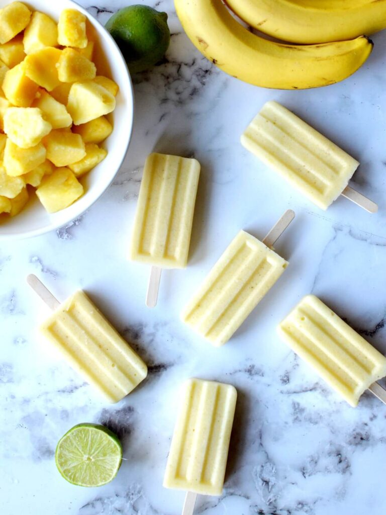 pineapple popsicles laying on a counter with limes, bananas and pineapple around it