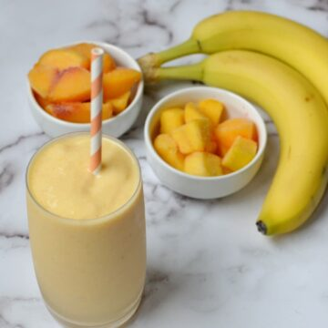 A banana peach smoothie with fruit behind it