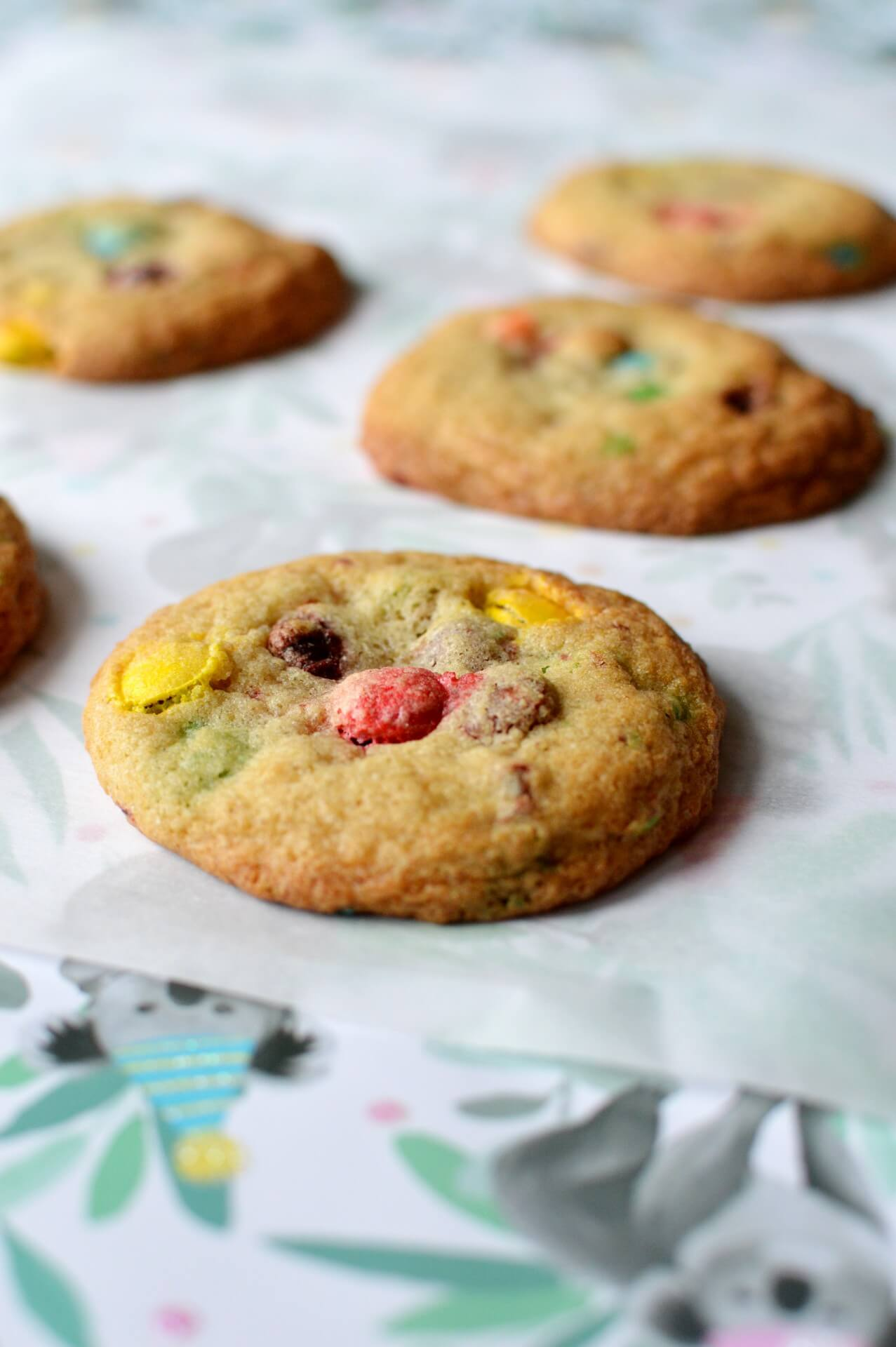 Five gluten free M&M cookies laying on a piece of parchment paper.
