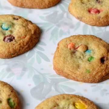 Gluten free m&m cookies laying flat on parchment paper