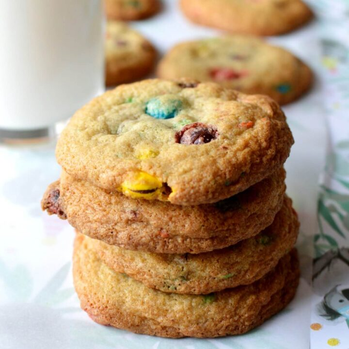 A stack of gluten free cookies with a glass of milk behind it