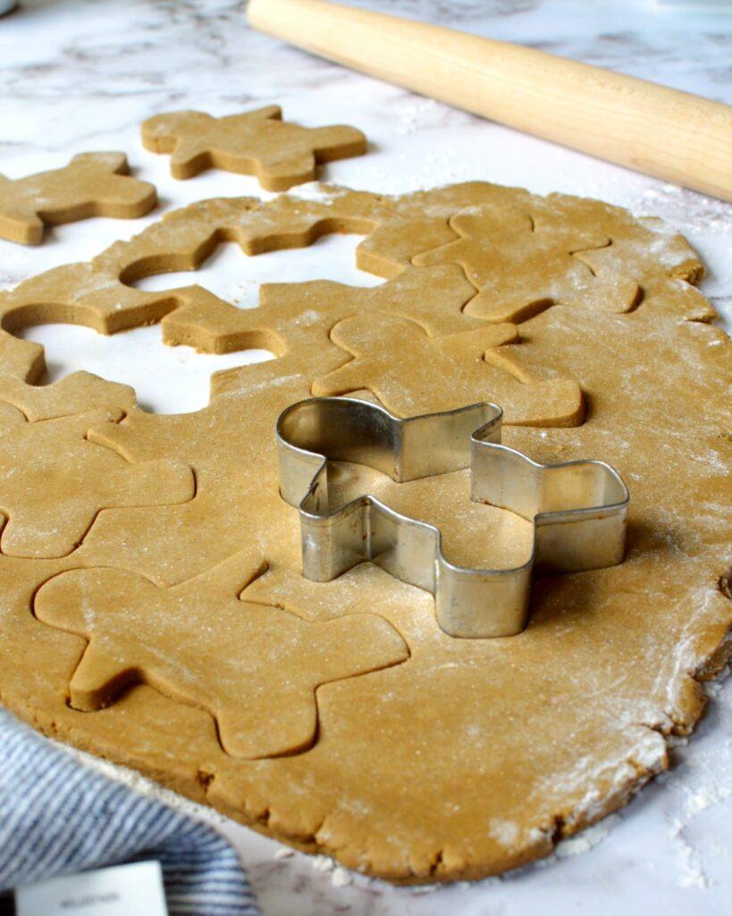 Gingerbread dough getting cut into gingerbread men