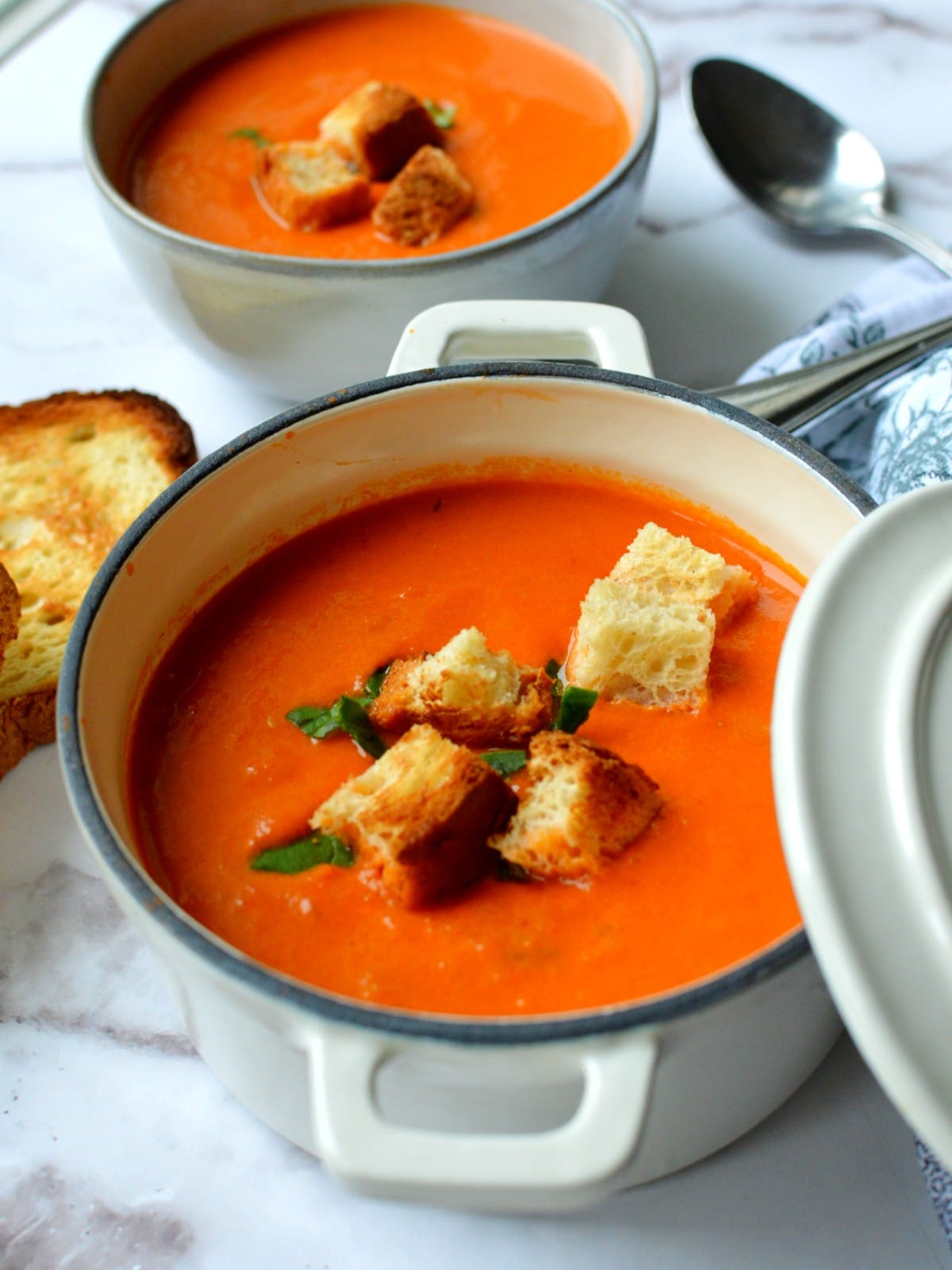 A bowl of tomato soup with croutons