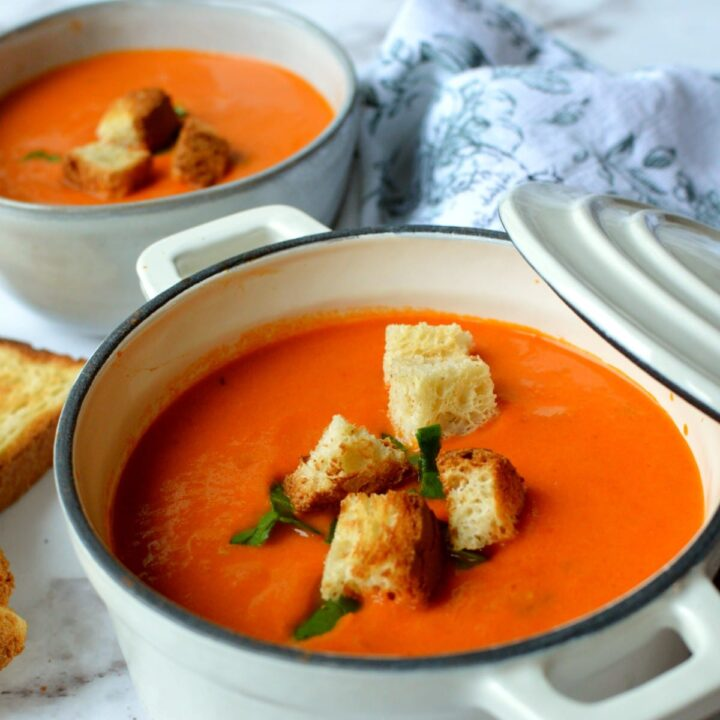 a pot of tomato bisque with croutons
